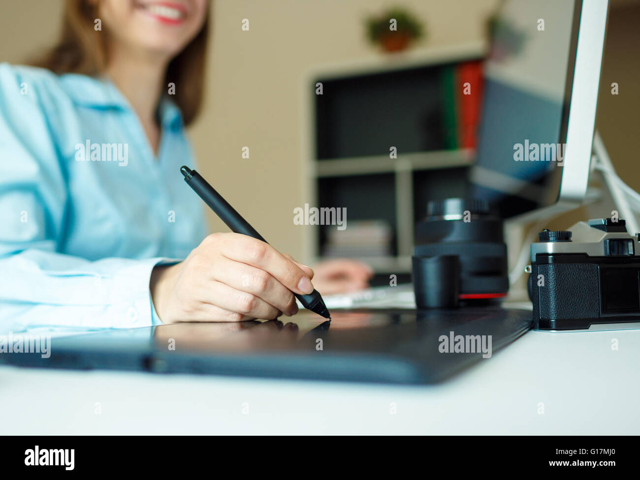 Young woman artist drawing something on graphic tablet at the home office - Stock Image