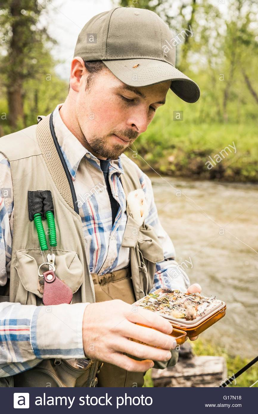Man by river selecting fishing fly from box - Stock Image