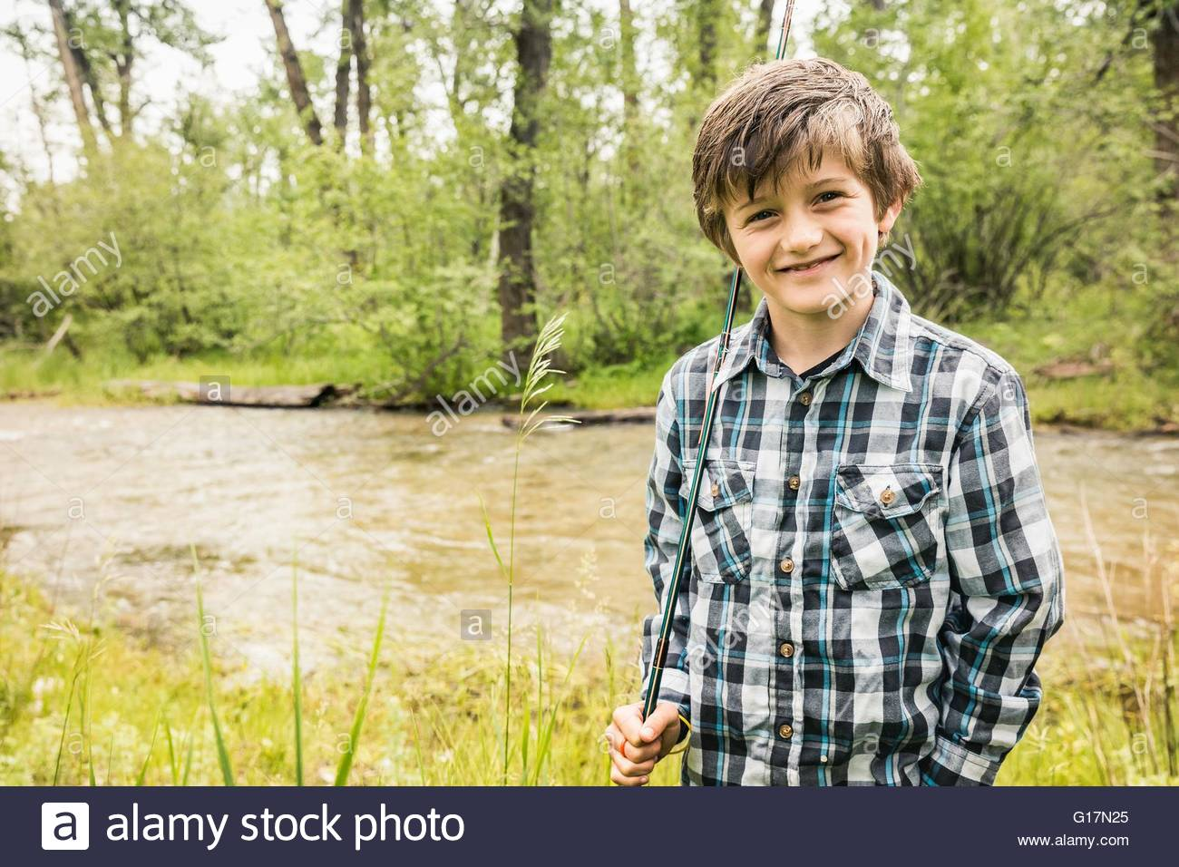 Boy wearing plaid shirt holding fishing rod by river looking at camera smiling - Stock Image