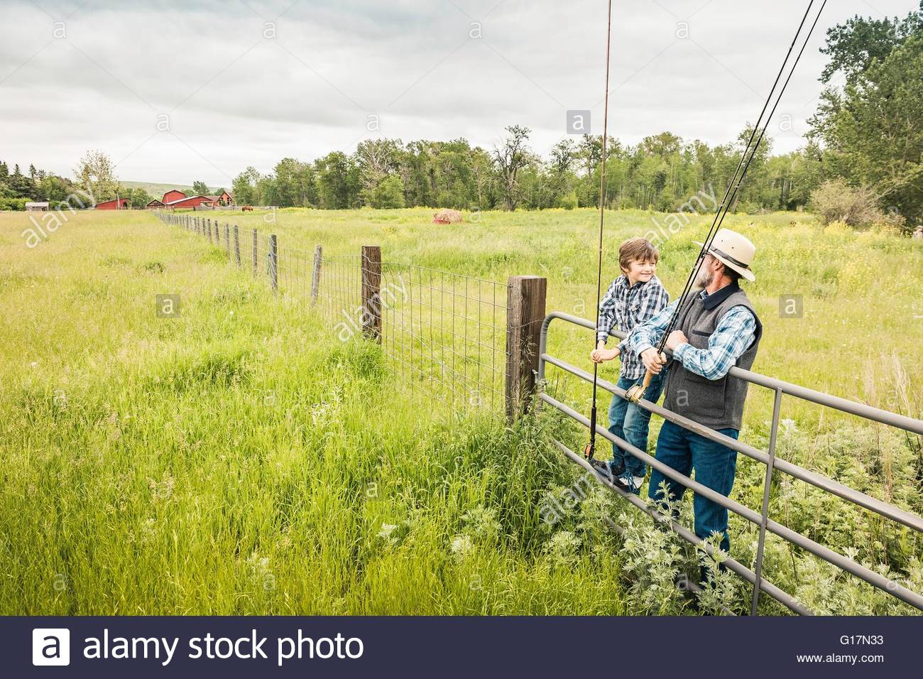 Man and boy holding fishing rods resting on gate in field - Stock Image