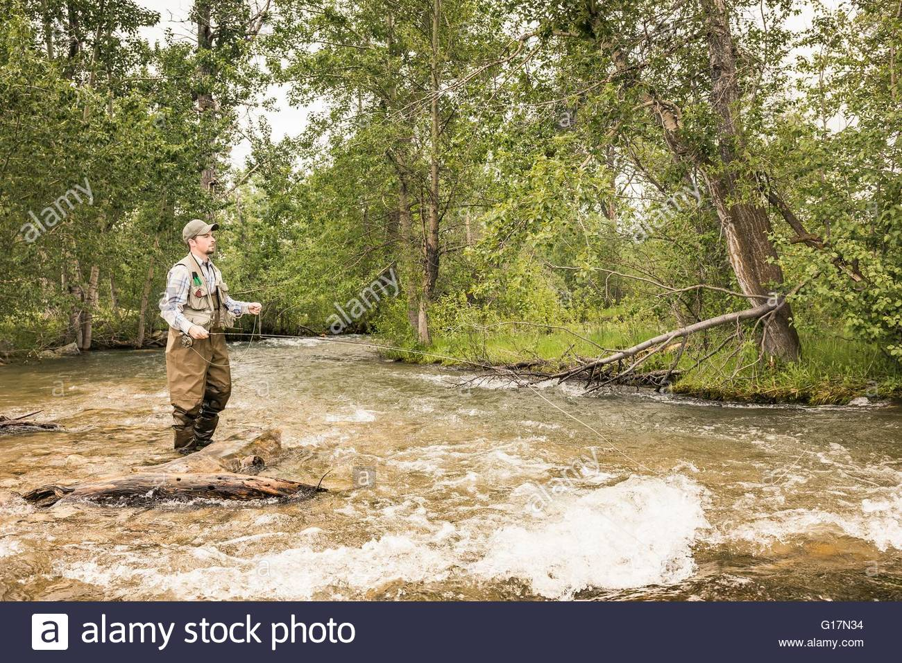 Man wearing waders ankle deep in water fishing - Stock Image