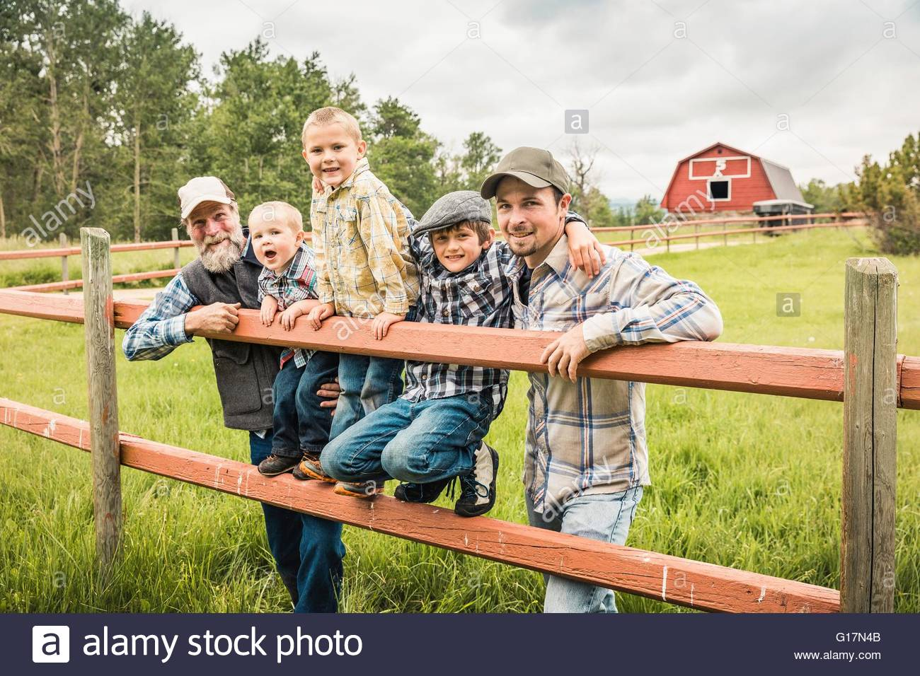 Multi generation family standing behind fence on farm looking at camera smiling - Stock Image