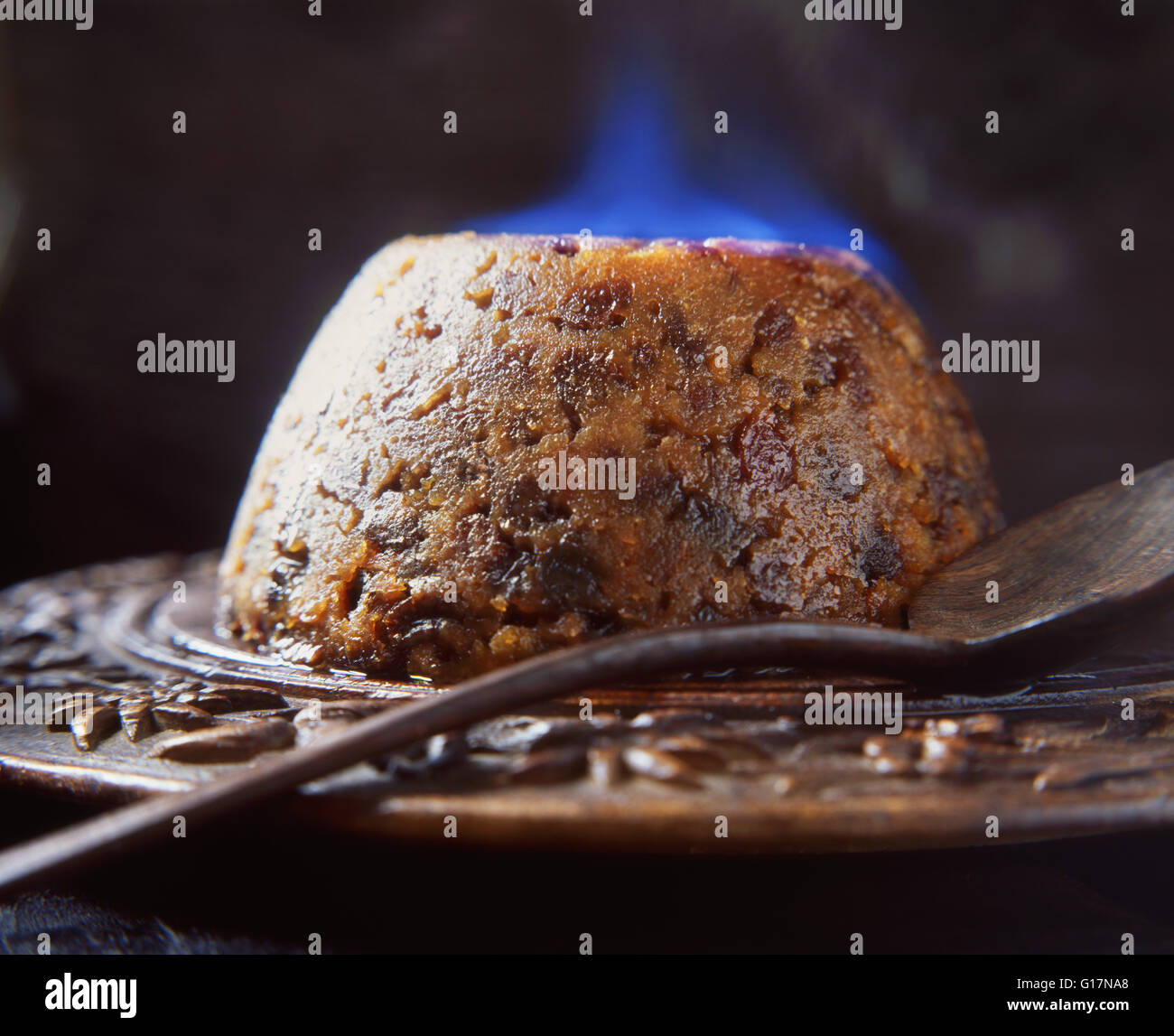 Flaming brandy Christmas pudding on wooden board Stock Photo