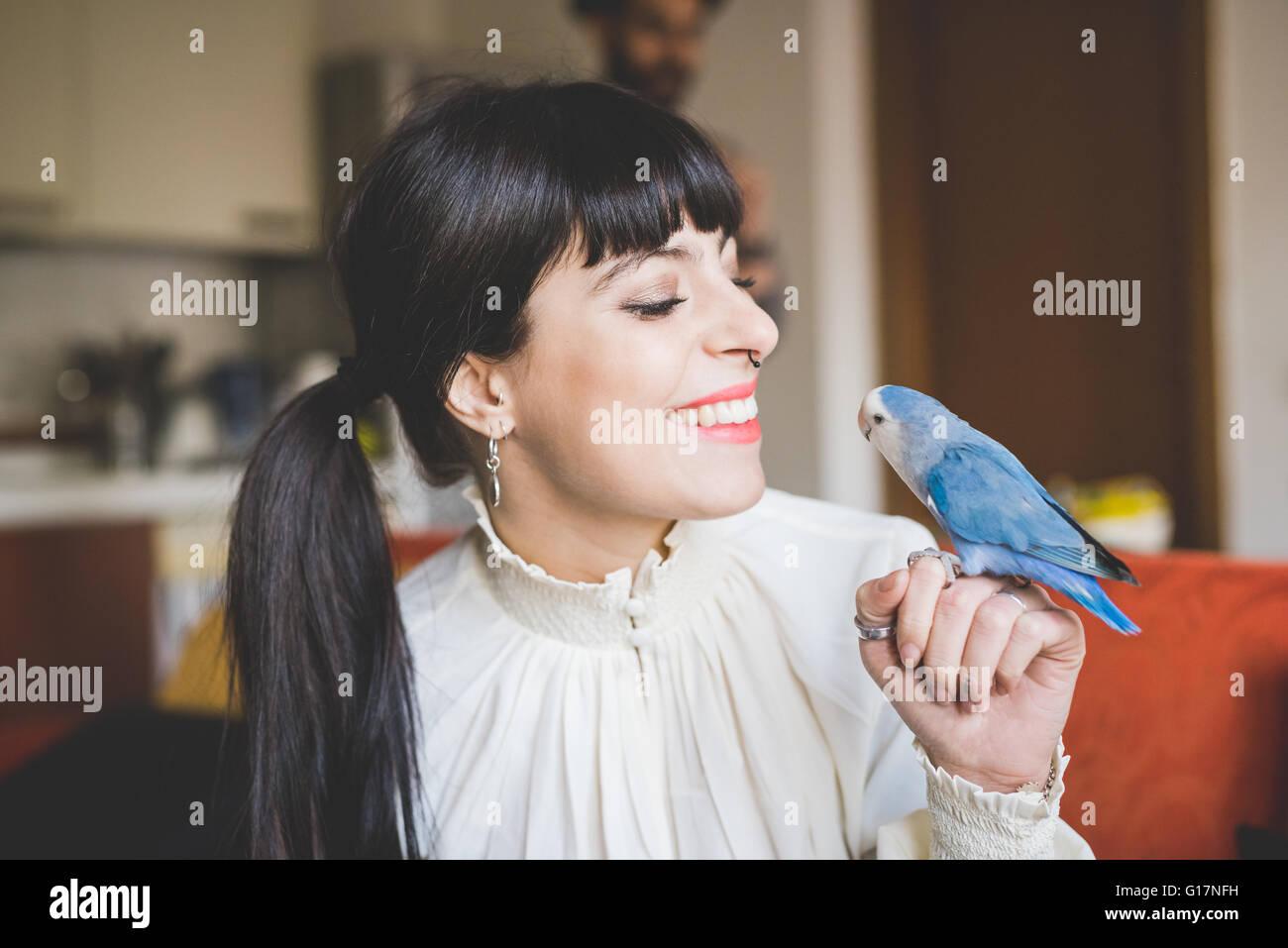 Young woman smiling at pet bird indoors - Stock Image