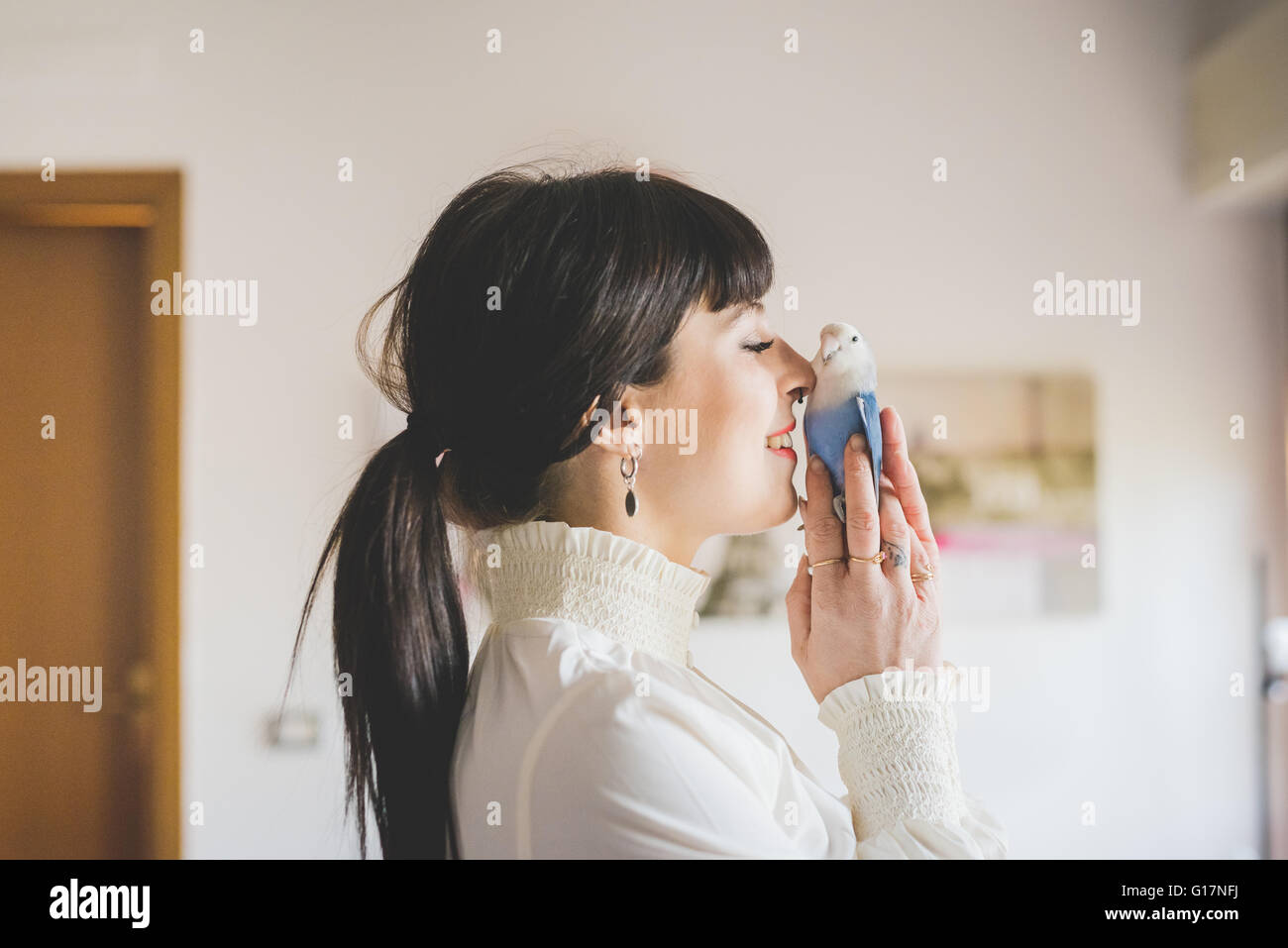 Young woman holding pet bird indoors - Stock Image
