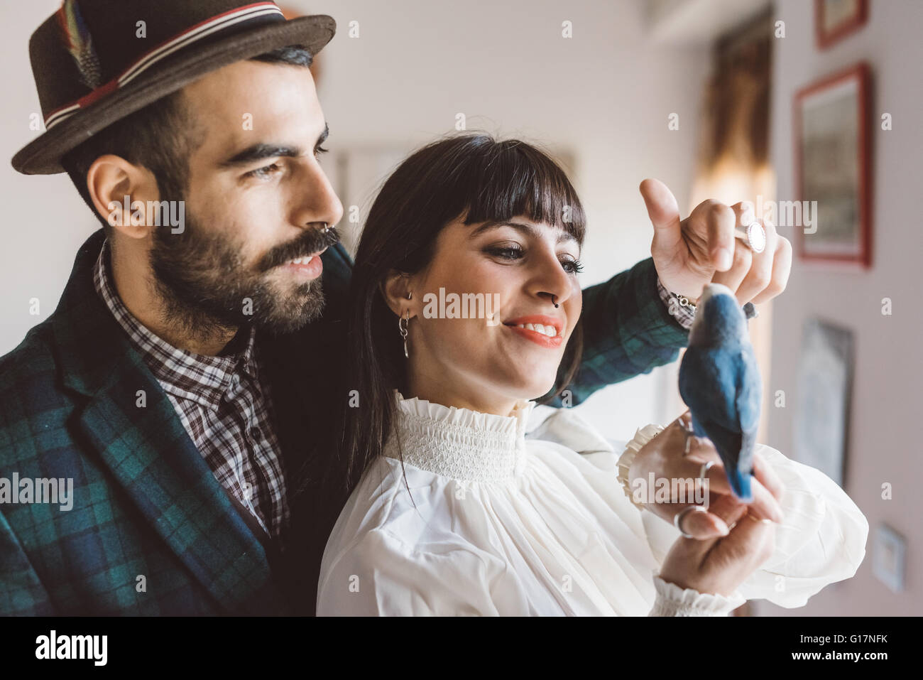 Young couple playing with pet bird indoors - Stock Image