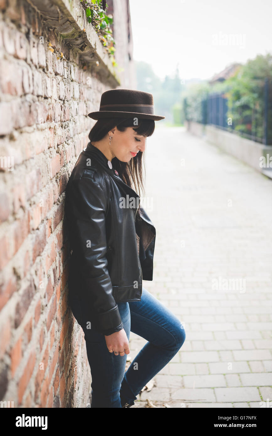Young woman leaning against brick wall - Stock Image