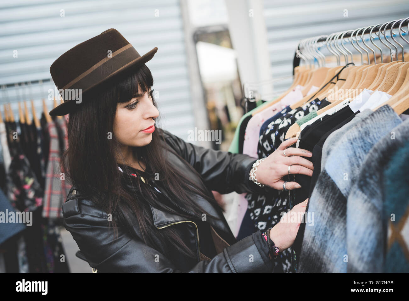 Young woman browsing clothes at market - Stock Image