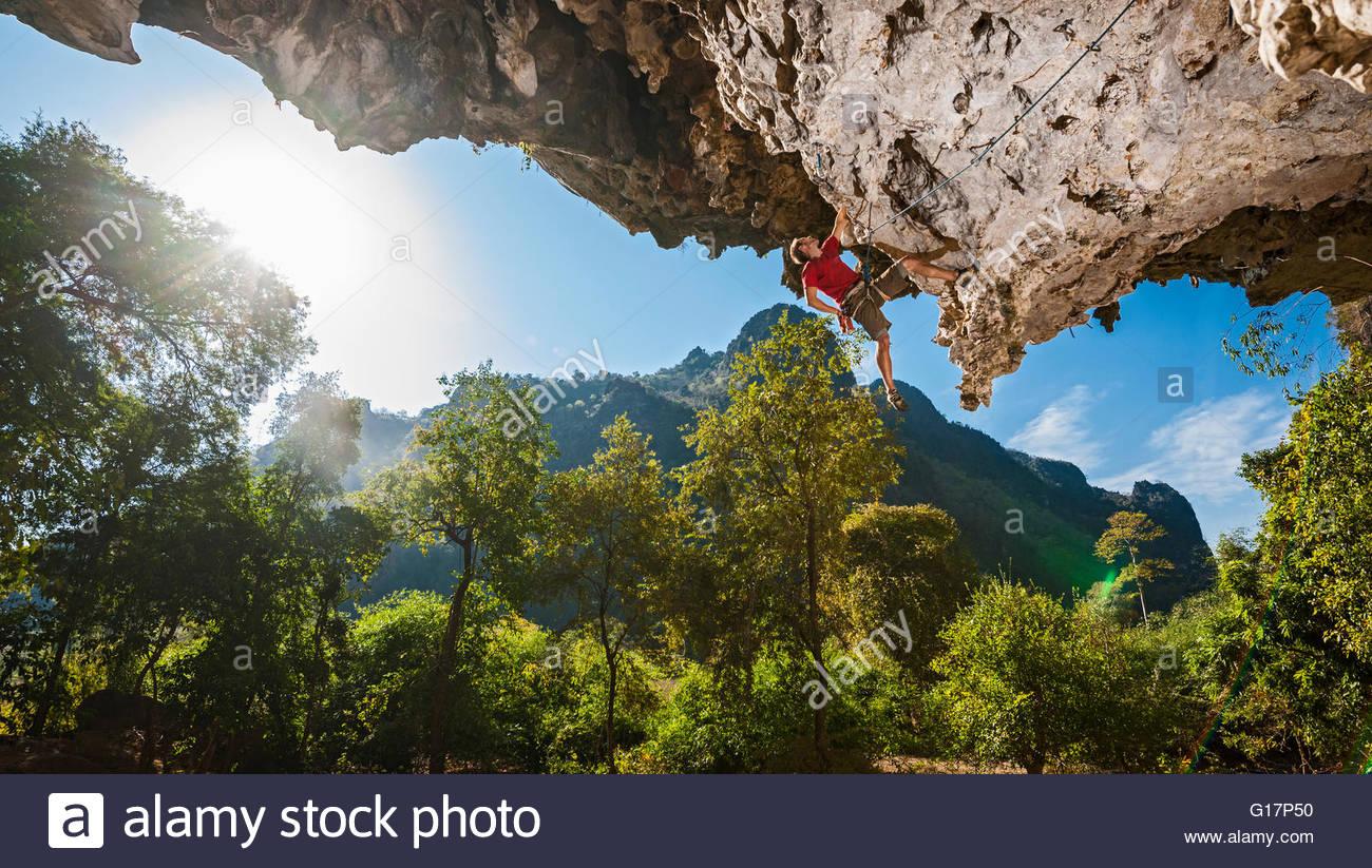 Young man rock climbing, close to Thakhek, Khammouane, Laos - Stock Image