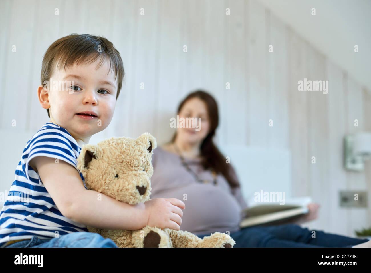 Baby boy holding teddy bear looking at camera - Stock Image