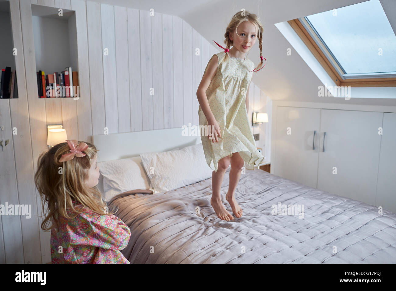 Girl jumping on bed in loft room - Stock Image