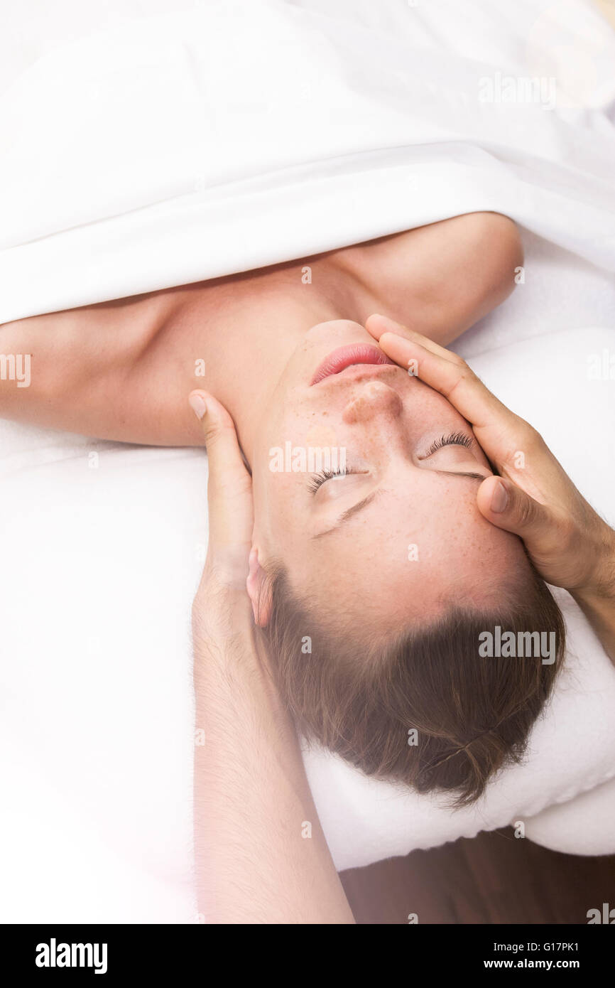 Male masseurs hands massaging head of young woman in spa Stock Photo