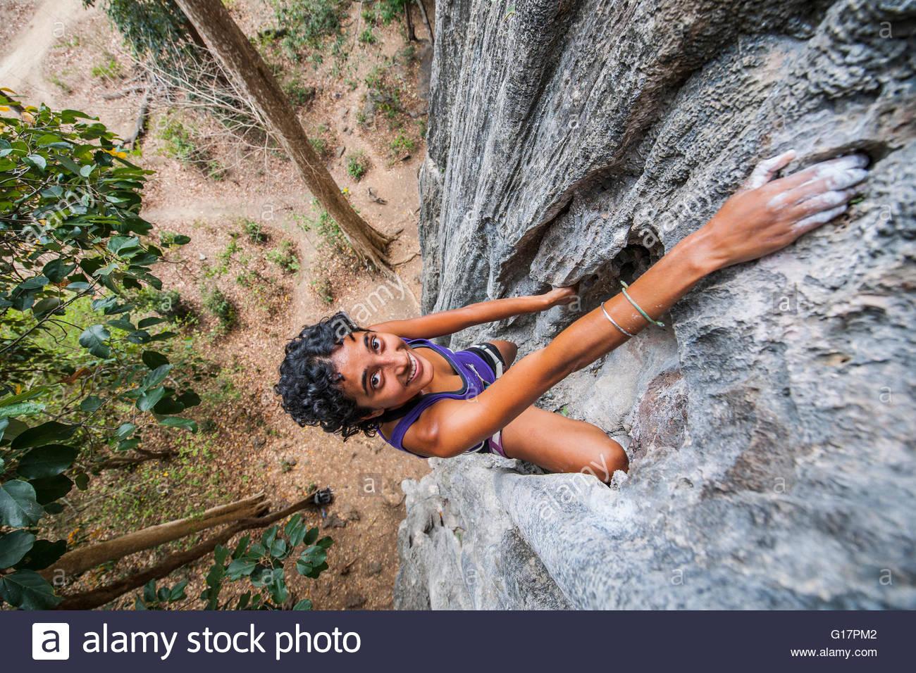 High angle portrait of young woman sport climbing rock face, Thakhek, Khammouane, Laos - Stock Image