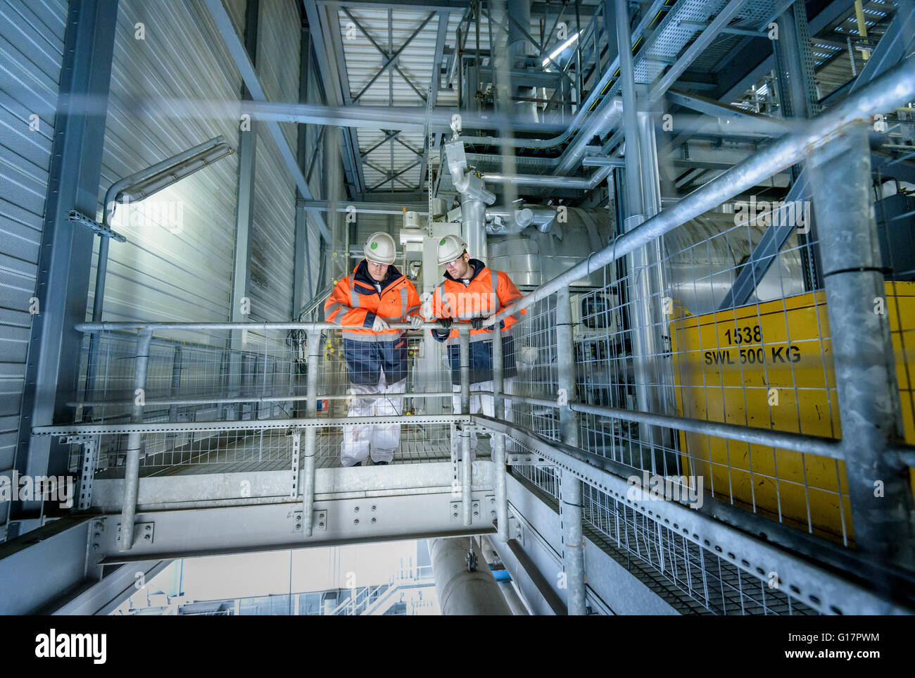 Workers on high level walkway in gas-fired power station - Stock Image