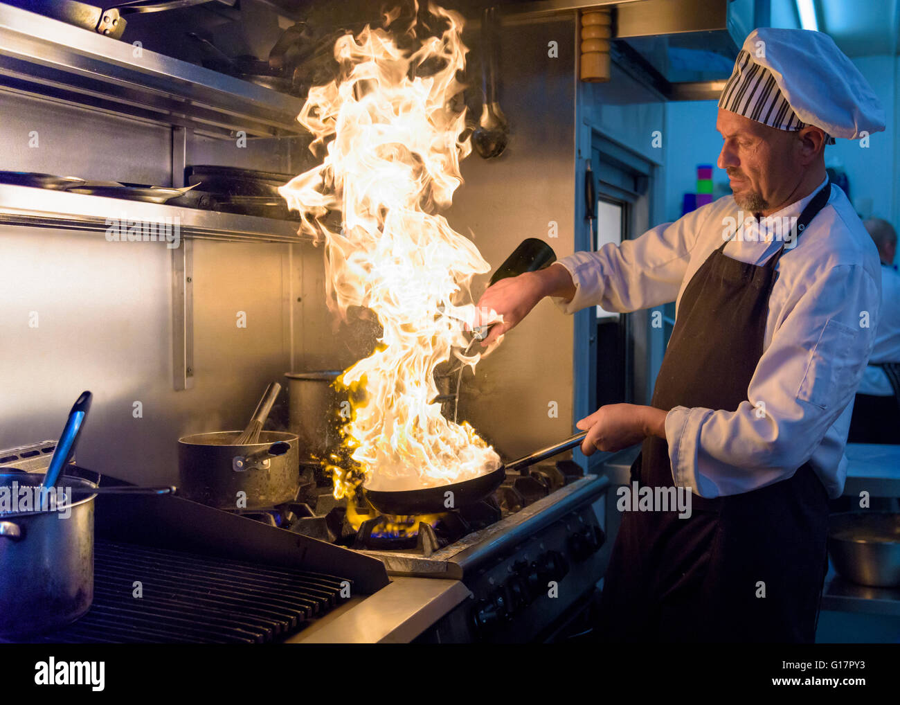 Chef with pan of flames in traditional Italian restaurant kitchen - Stock Image