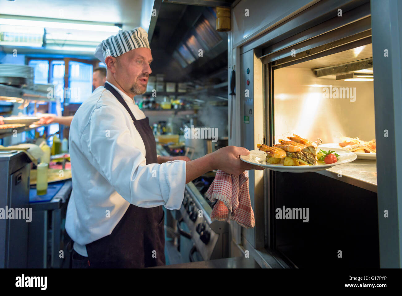 Chef placing dish in lift in traditional Italian restaurant kitchen - Stock Image