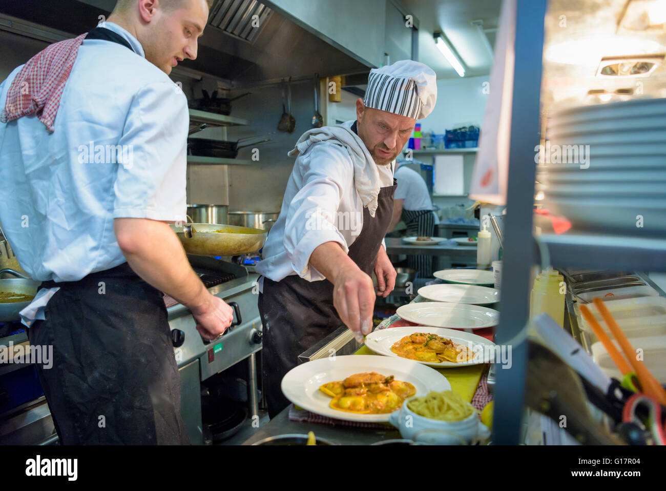 Chefs plating up lobster ravioli in traditional Italian restaurant kitchen - Stock Image