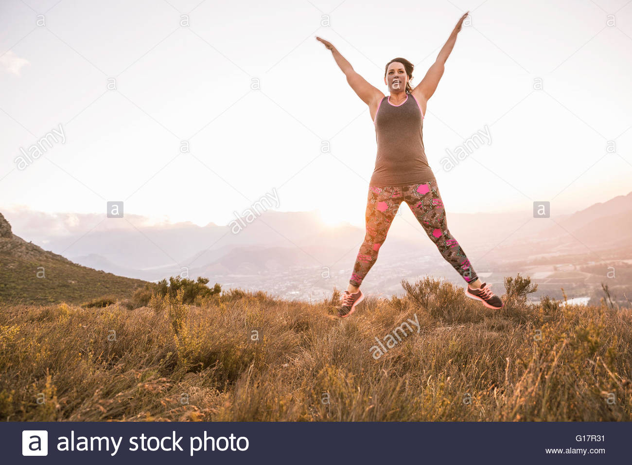Plus size woman on mountain wearing sports clothing doing star jump in mid air - Stock Image