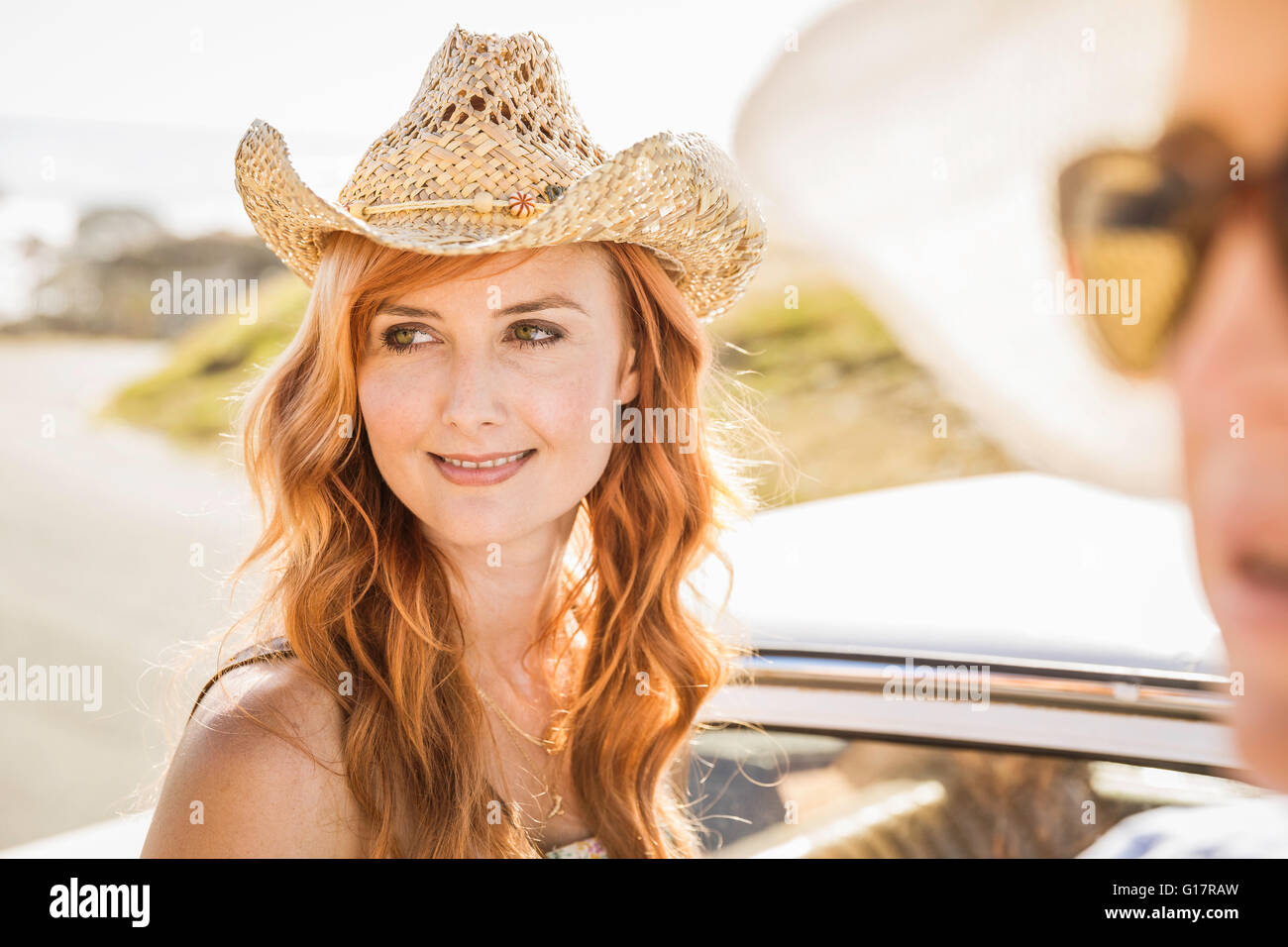 Mid adult woman wearing straw hat on coast road da433eac58a