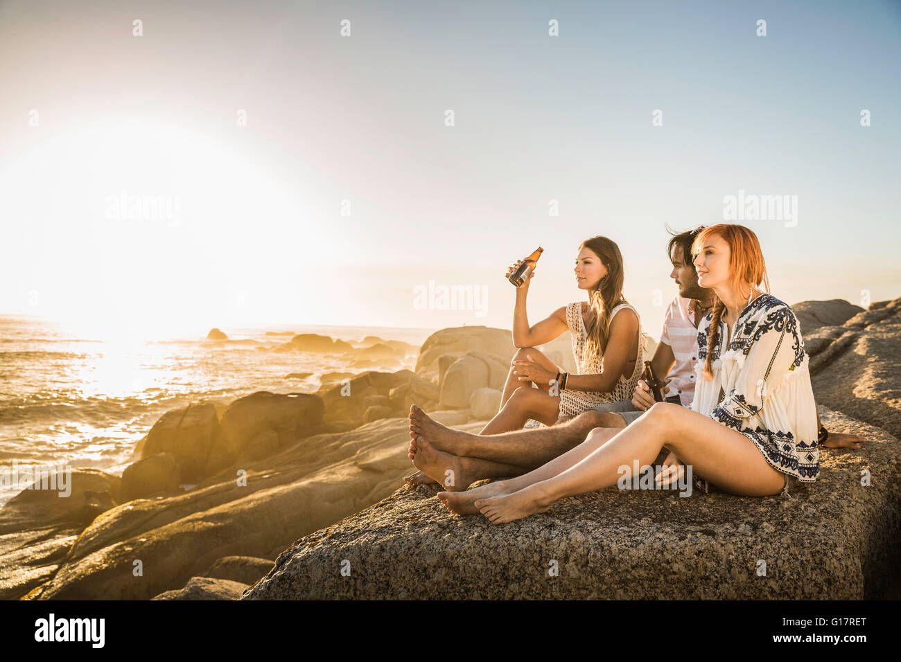 Three mid adults sitting on beach looking out at sunset, Cape Town, South Africa - Stock Image