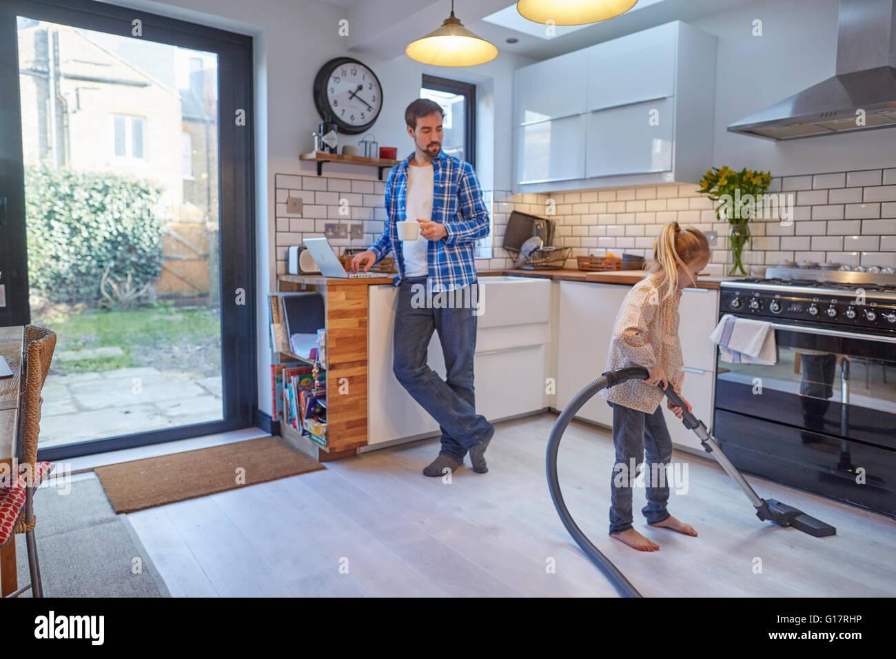 Attrayant Father Watching Daughter Vacuum Kitchen Floor