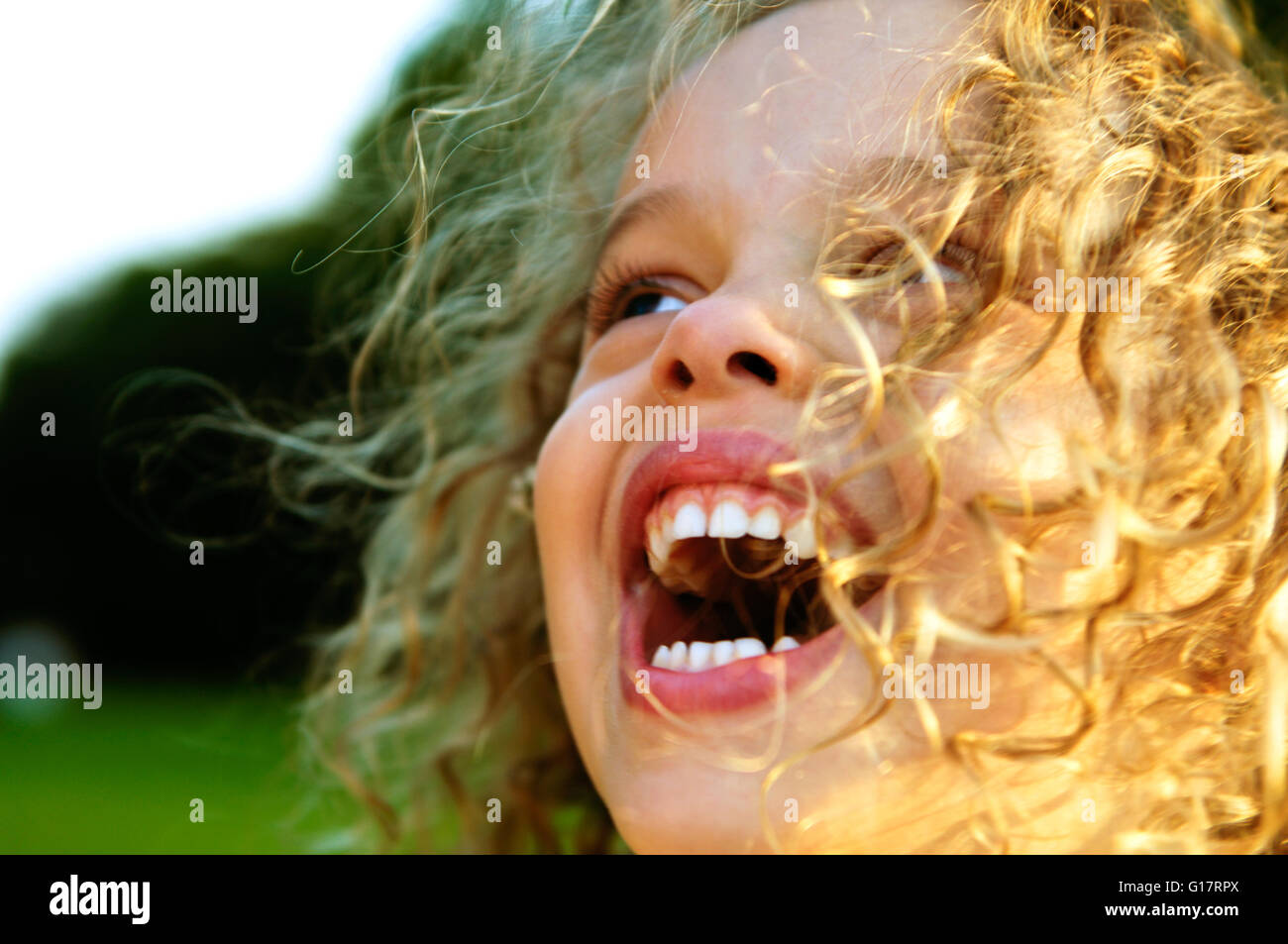 Close up of blond curly haired girl laughing - Stock Image