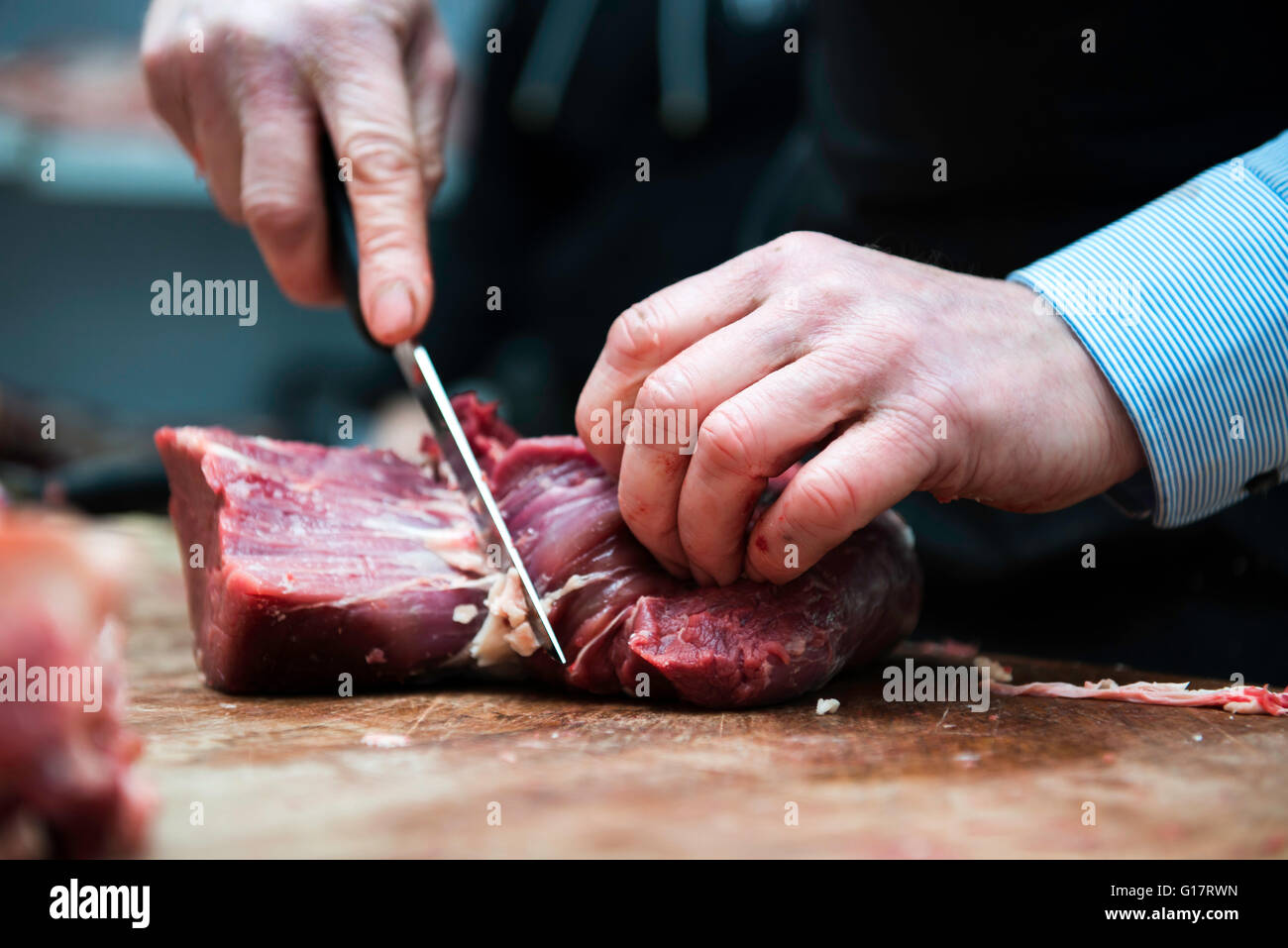 Butcher preparing meat in butcher's shop, close-up - Stock Image