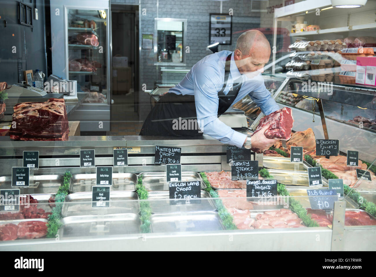 Butcher preparing window display in butcher's shop Stock Photo