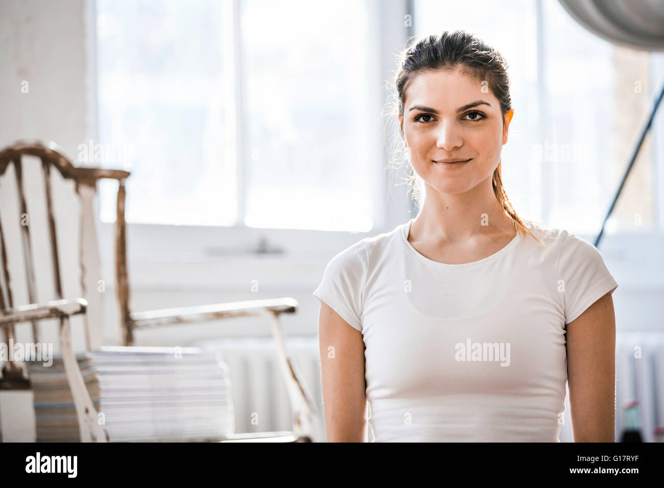 Portrait of beautiful young woman in shabby chic apartment - Stock Image