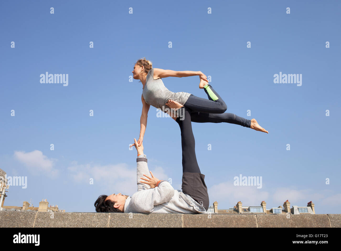 Man and woman practicing acrobatic yoga on wall Stock Photo