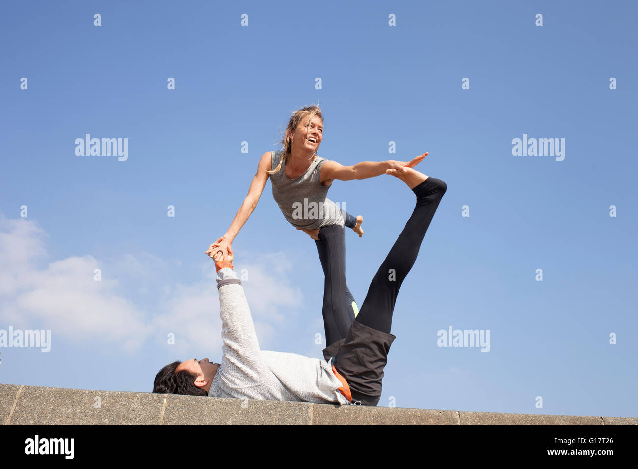Man and woman on wall practicing acrobatic yoga Stock Photo