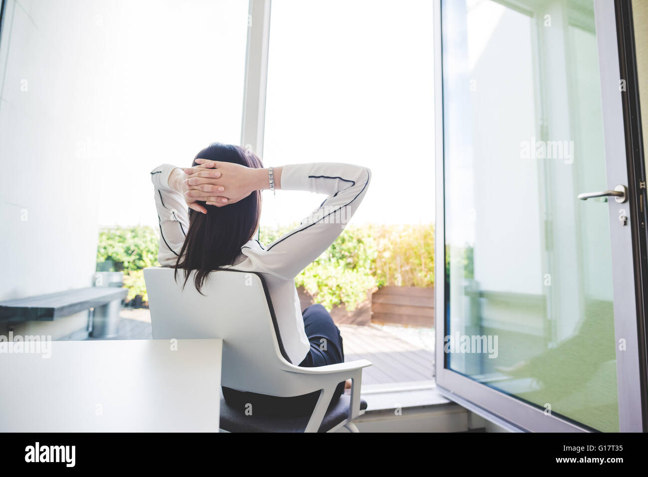 Young businesswoman relaxing in office looking out of patio doors - Stock Image
