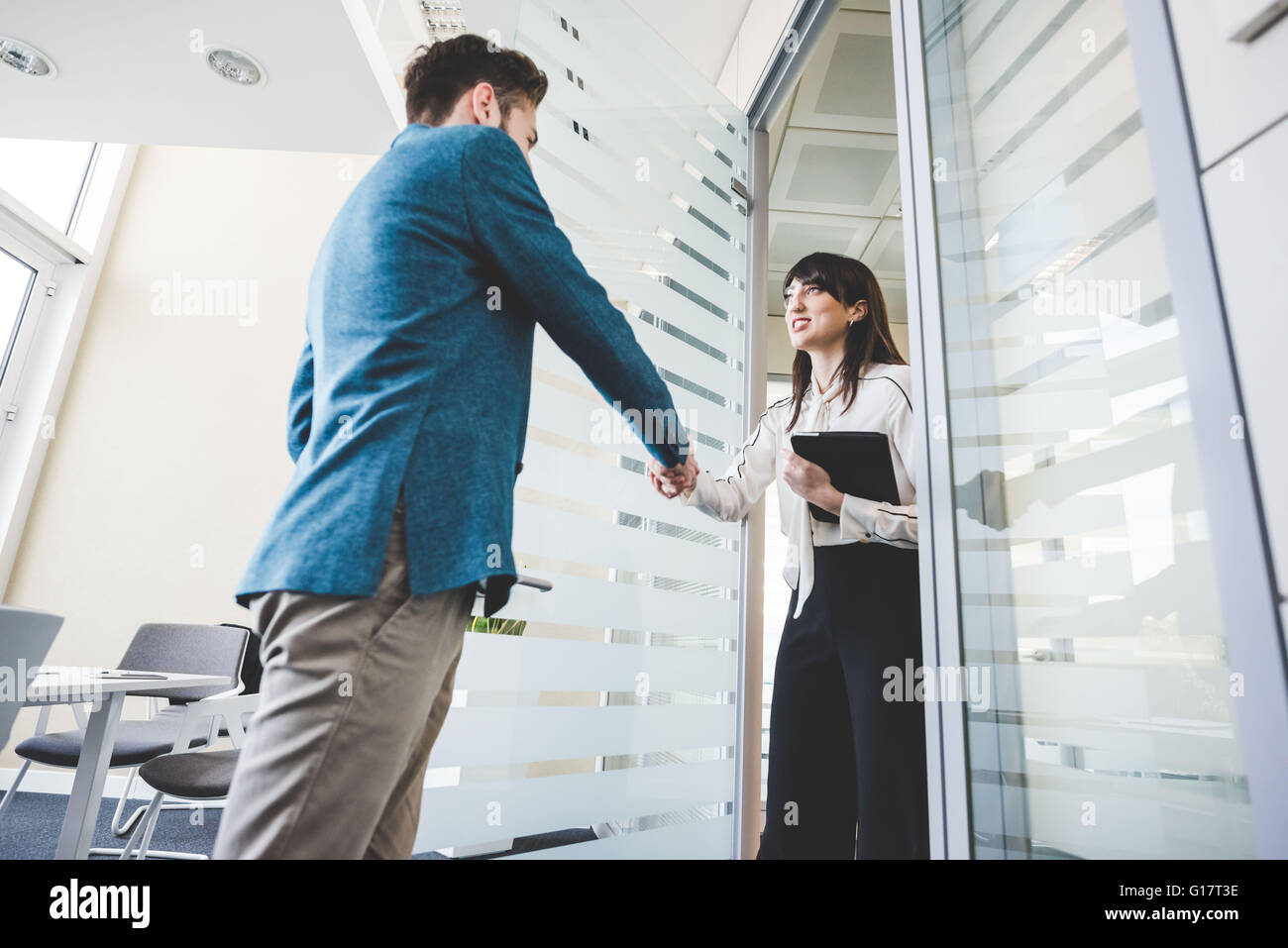 Young businesswoman and client shaking hands in office - Stock Image