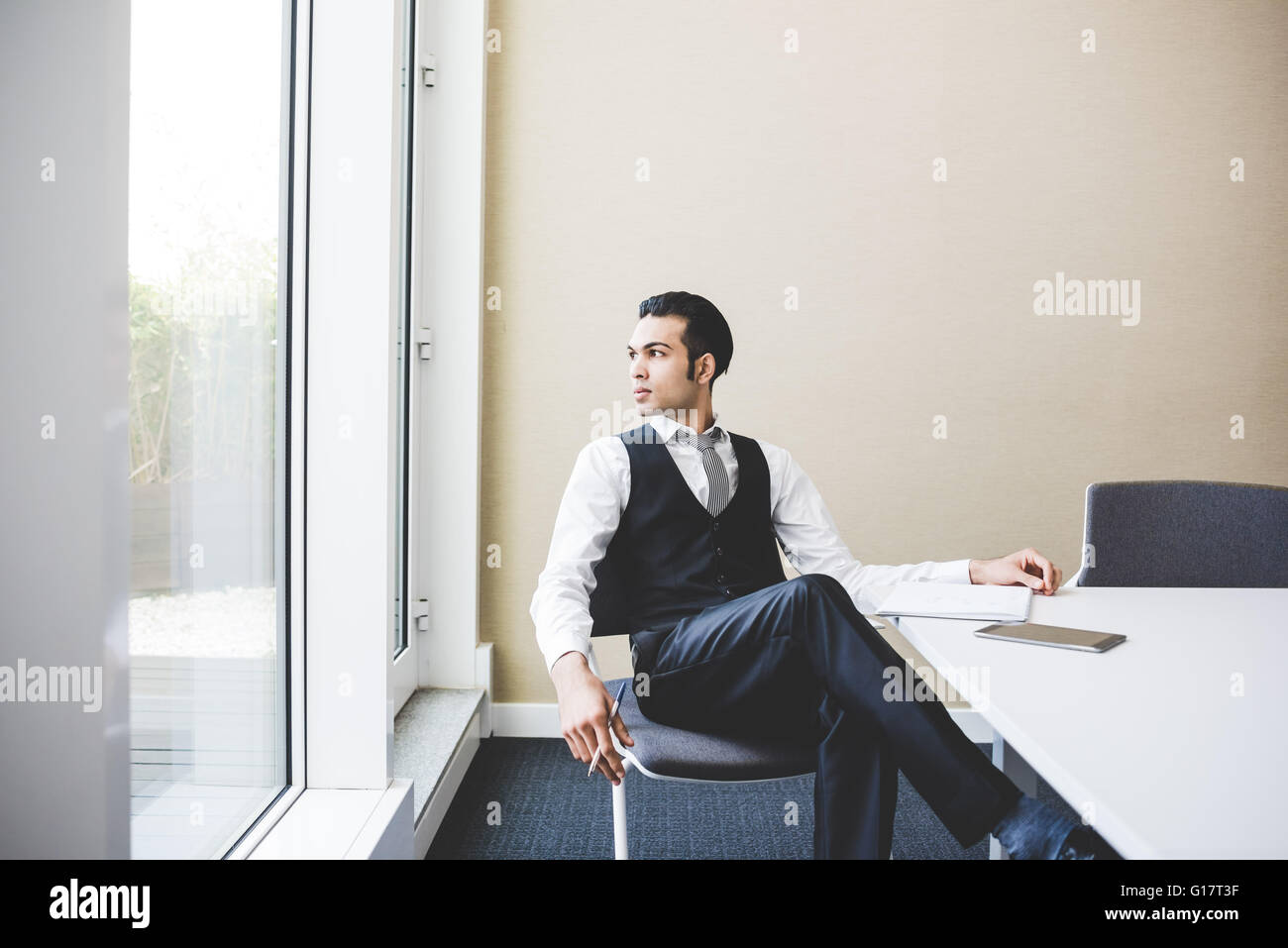 Young businessman looking over his shoulder through office window - Stock Image