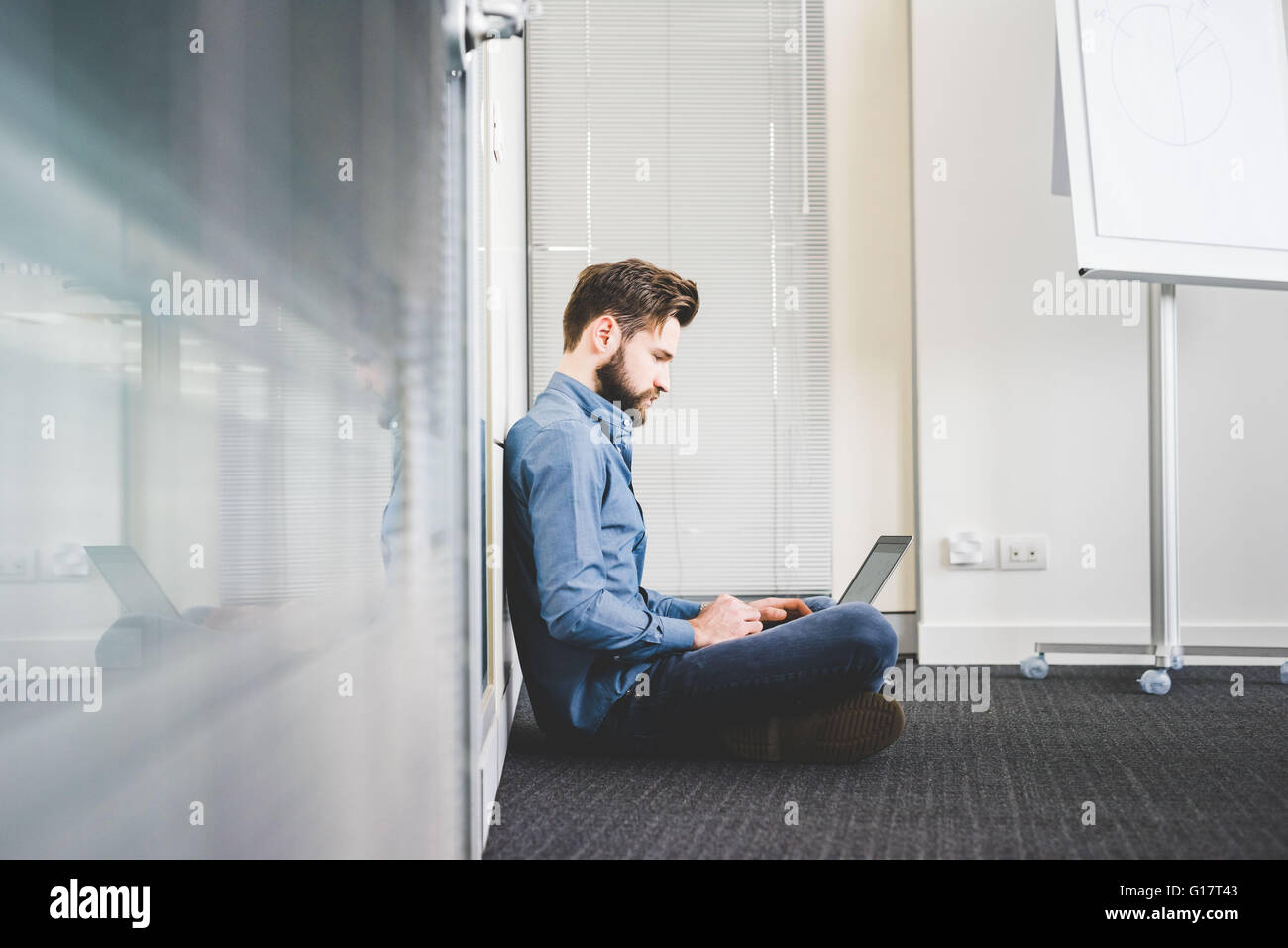Young male sitting on office floor using laptop - Stock Image
