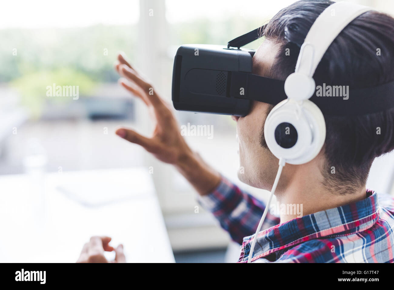 Young male designer testing virtual reality headset in office - Stock Image