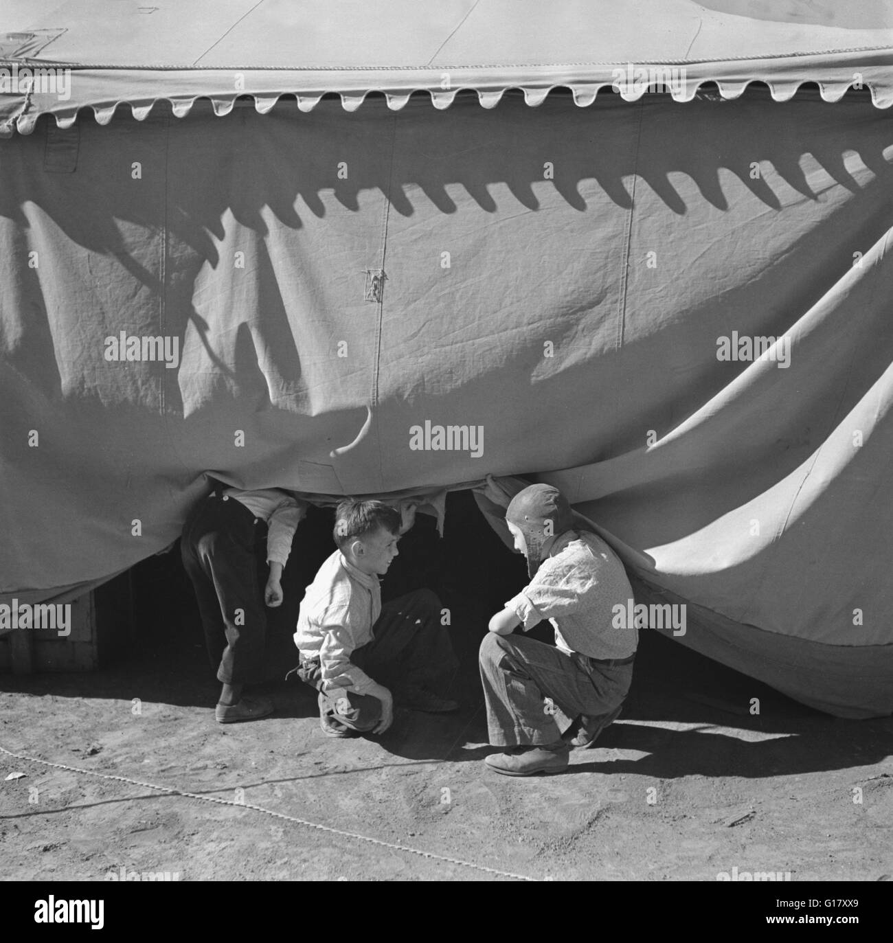 Children Sneaking Under Circus Tent, Roswell, New Mexico, USA, Arthur Rothstein for Farm Security Administration, - Stock Image