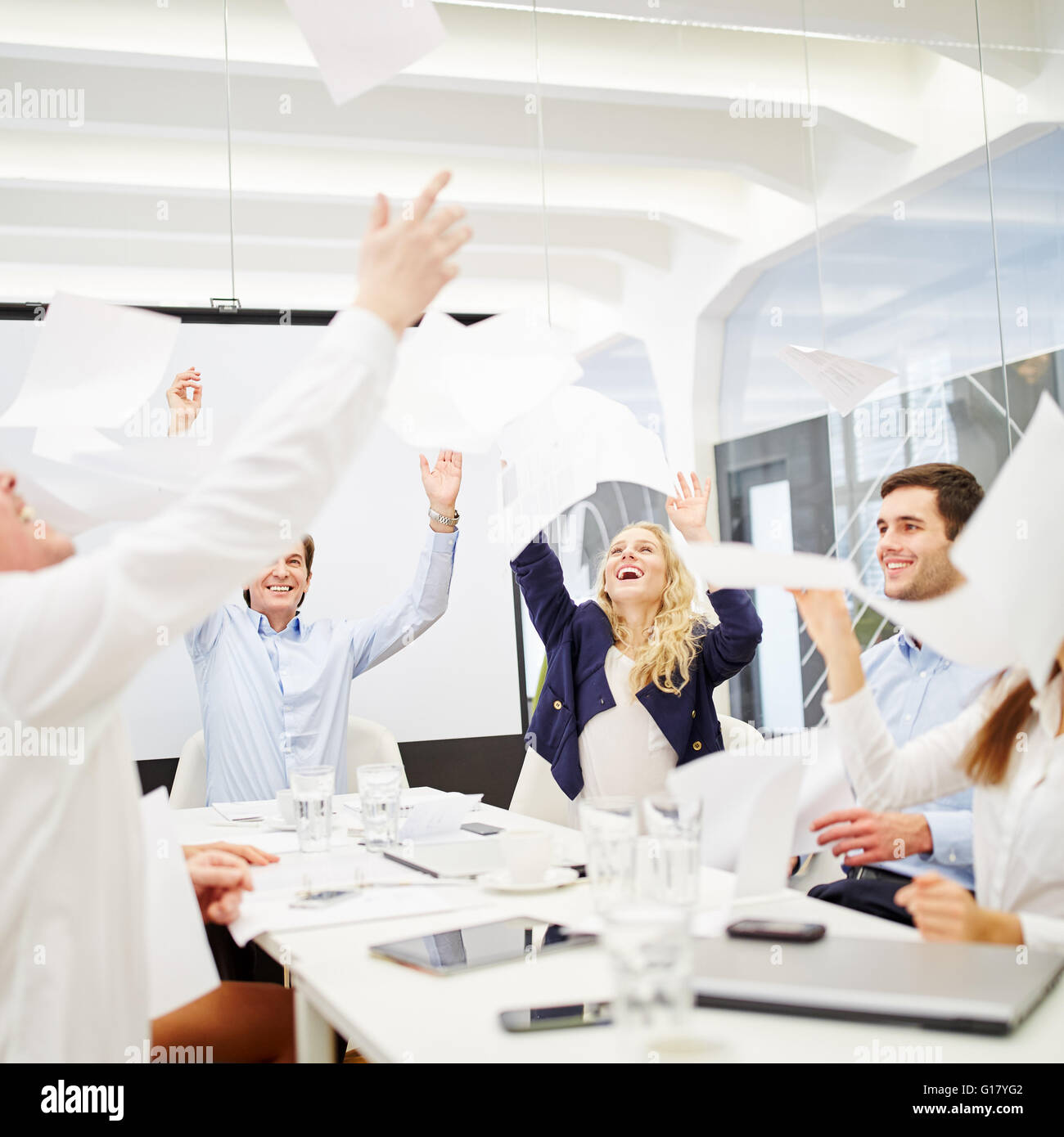 Business people celebrates their success and throws sheets of paper in the air during a business meeting - Stock Image