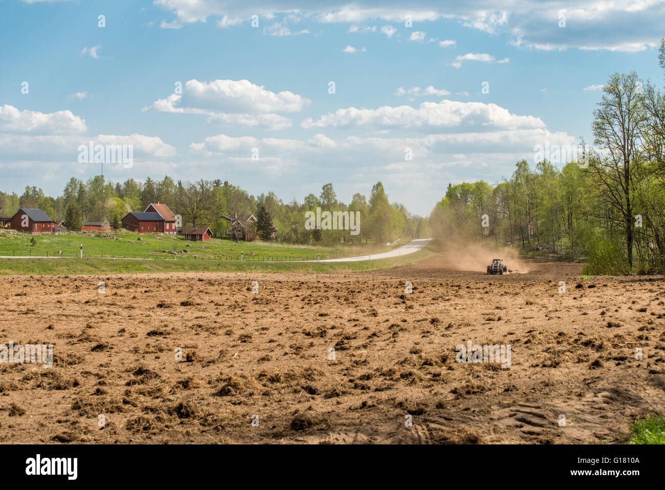 Tractor plowing fields during spring in county Östergötland, Sweden. - Stock Image