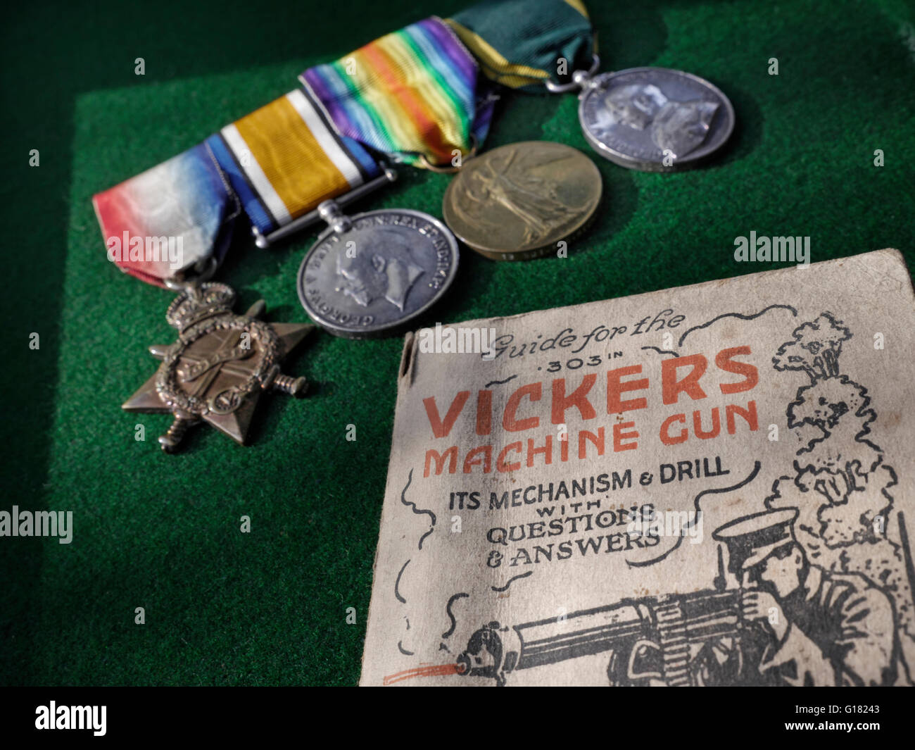 WW1 British Service medals next to instruction manual for 1914 Vickers .303 machine gun - Stock Image