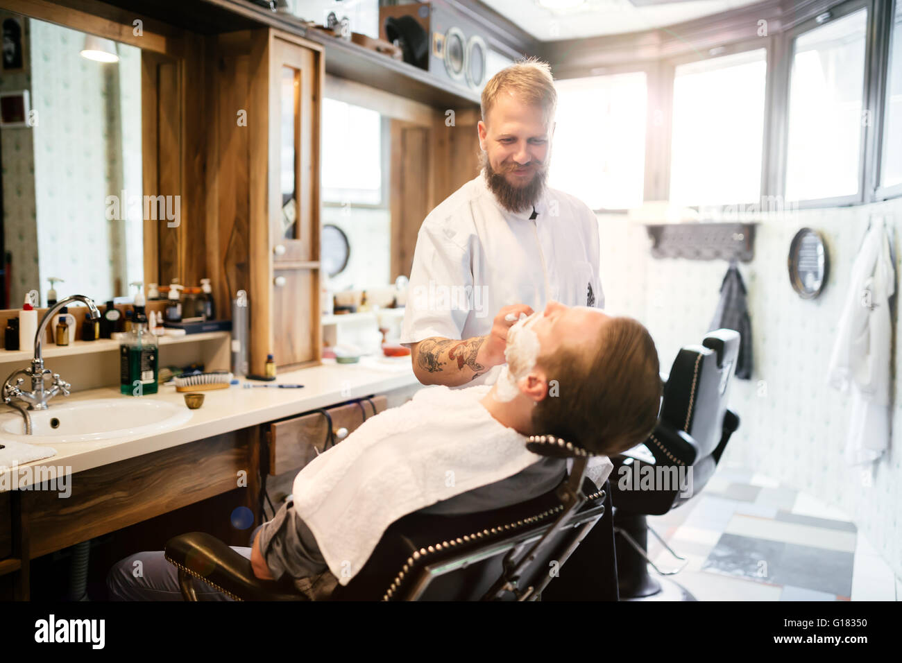 Male receiving hair beard treatment in barber shop - Stock Image