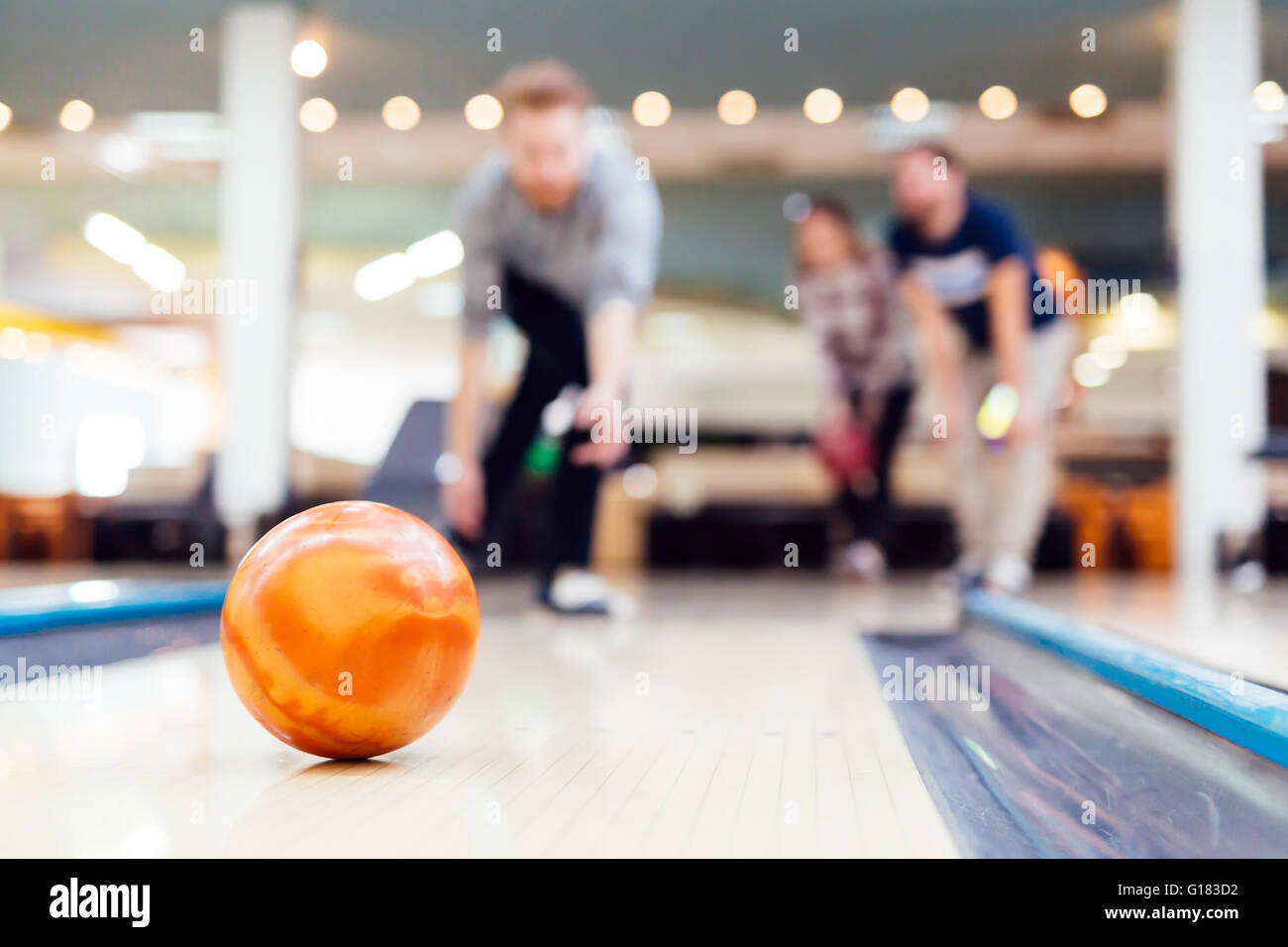 Friends enjoying recreational  bowling at club - Stock Image