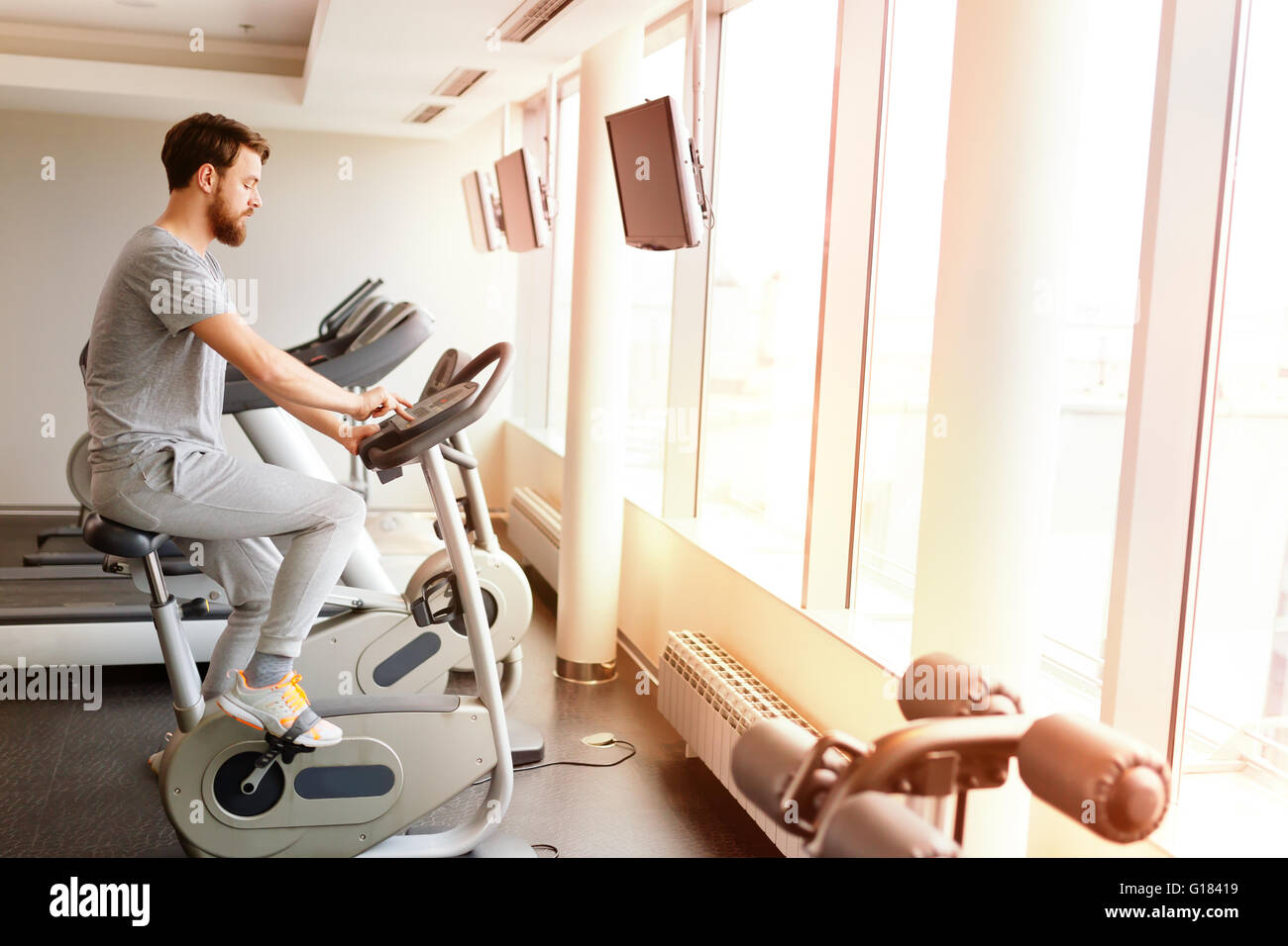 Sportive male exercising on bicycle in gym - Stock Image