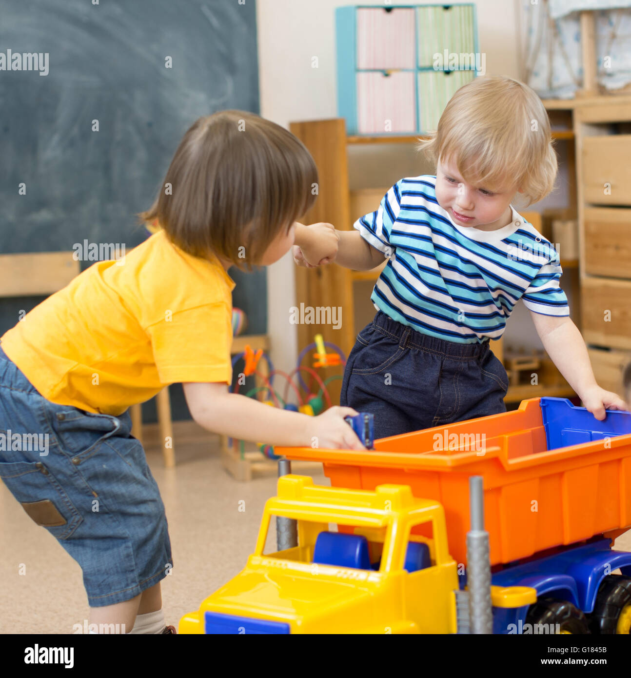 two kids conflict or struggling for toy truck in kindergarten - Stock Image