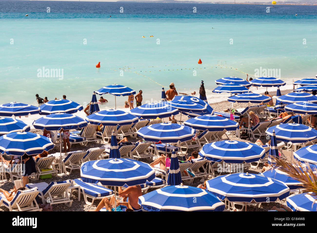 Baie Des Anges and blue sun umbrellas on beach, Nice, Cote D'Azur, France - Stock Image