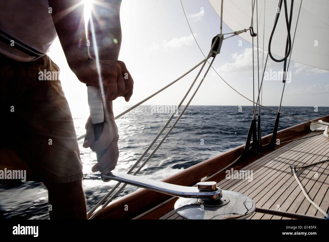 Man turning winch handle on classic sail yacht - Stock Image