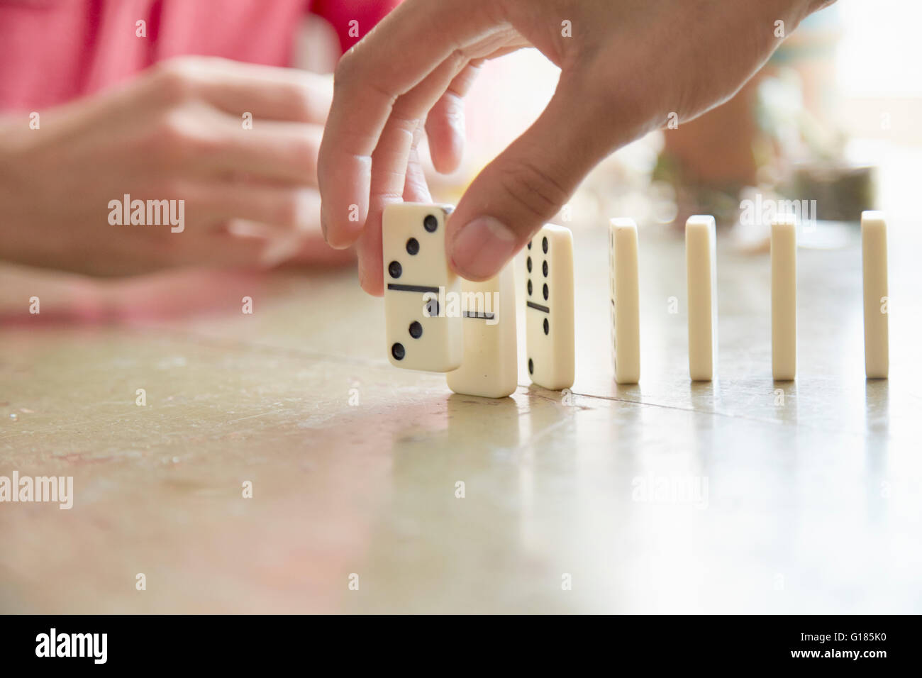 Cropped view of mans hand placing domino on edge - Stock Image