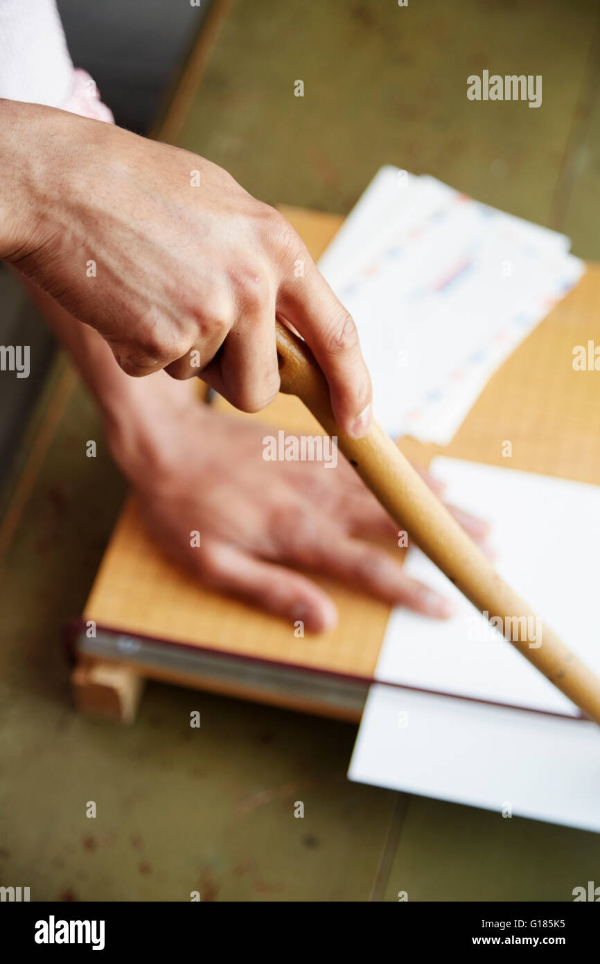 High angle view of mans hands using guillotine - Stock Image