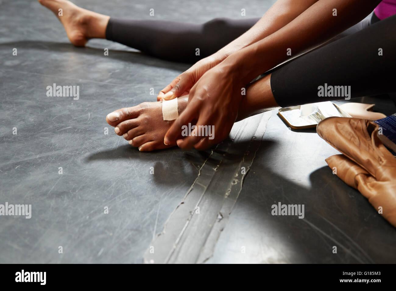 Ballet dancer putting on plaster on foot - Stock Image