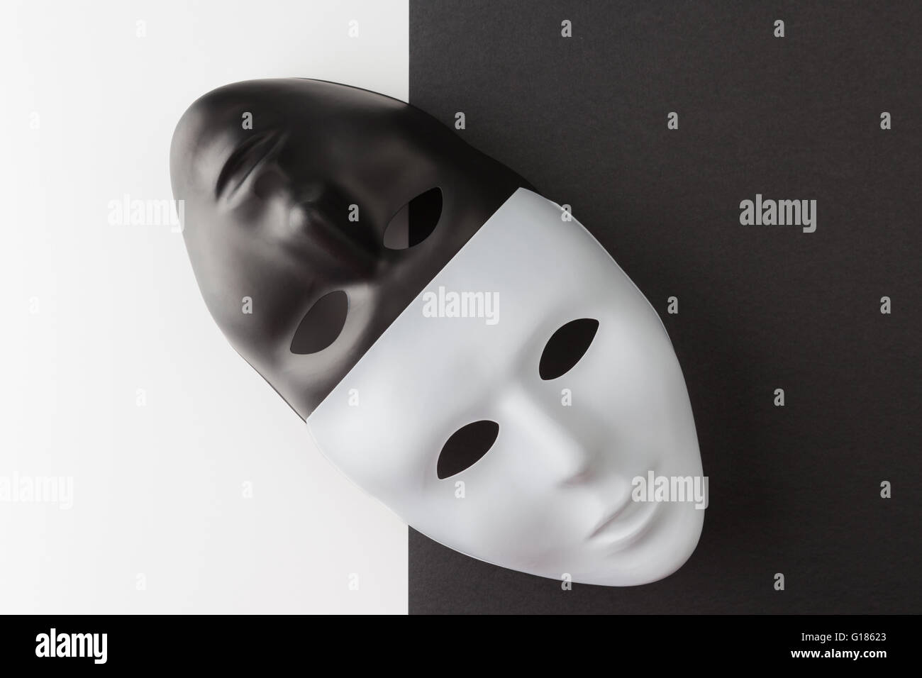 Black and white masks placed diagonally on contrasting background. Web anonymity concept - Stock Image